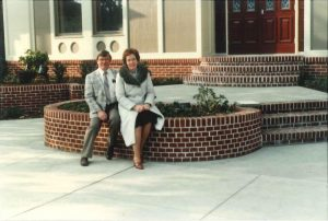 1983 couple in front of Ruhl Insurance building