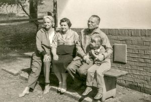 black and white photo of family sitting on a bench