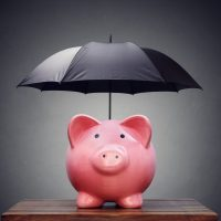 piggy bank with black umbrella over it
