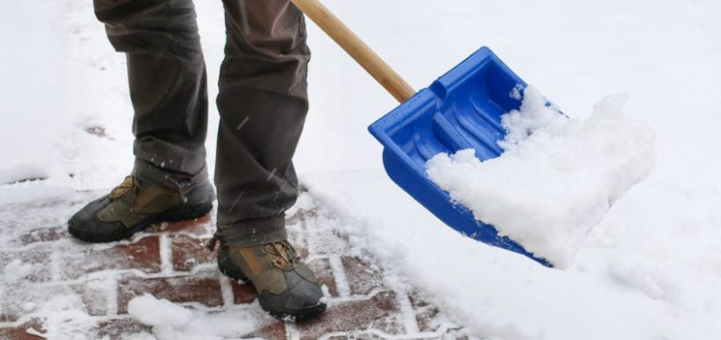 avoid an insurance claim - man clearing sidewalk after snow