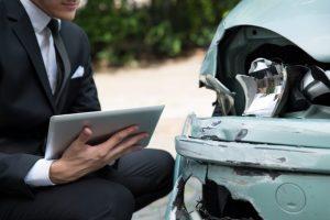 insurance claim - adjuster with tablet examining damaged car
