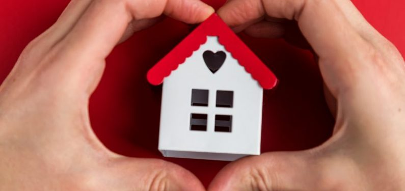 small home model in middle of hands shaped as a heart