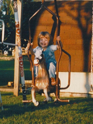 child on vintage horse swing