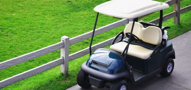golf cart parked next to a fence