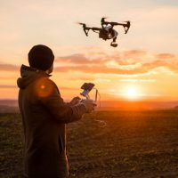 man operating a drone at sunset