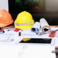 hard hats, blueprints, and designs on a table