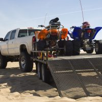 pickup truck and trailer with quads on a beach