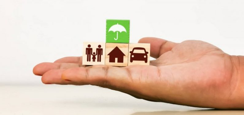insurance concept hand holding blocks with umbrella, house, car, and family icons